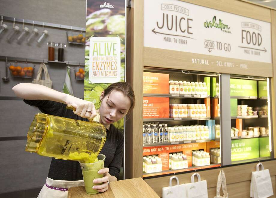Zarah Siewert pours a smoothie during Monday's grand opening of Evolution Fresh juice store. Photo: Stephen Brashear, Getty Images