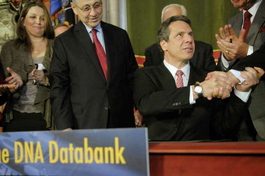 Governor Andrew Cuomo, right, shakes hands with a legislator as Ann M., left, from Queens, NY, and Assembly Speaker Sheldon Silver, center, look on after the Governor signed the DNA expansion bill on Monday, March 19, 2012 at the Capitol in Albany, N.Y.  Ann M. has been an advocated for the expansion of DNA collection for years.  Ann M. began her work to get the expansion of DNA collection shortly after her daughter's rape in her own bedroom by a man who broke into their home some years ago.  (Paul Buckowski / Times Union) Photo: Paul Buckowski