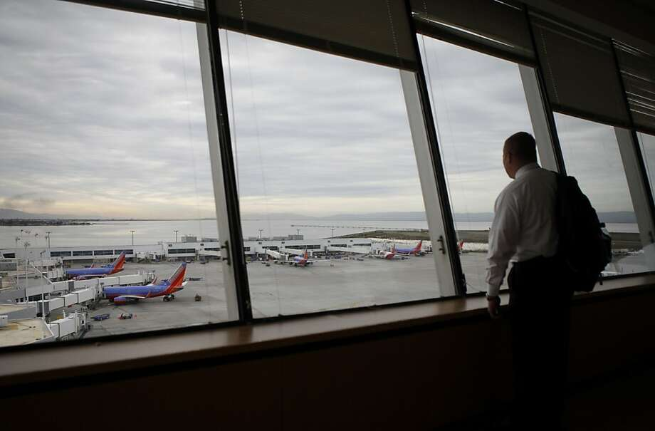 Chris Osterman of United Airlines looks down from the tower lounge at the planes at the Oakland airport. Photo: Sean Culligan, The Chronicle
