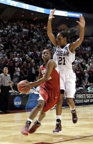 Arkansas' C'eira Ricketts, left, drives toward the basket as Texas A&M's Adaora Elonu (21) defends during the second half of an NCAA tournament second-round women's college basketball game Monday, March 19, 2012, in College Station. Texas A&M beat Arkansas 61-59. Photo: Associated Press