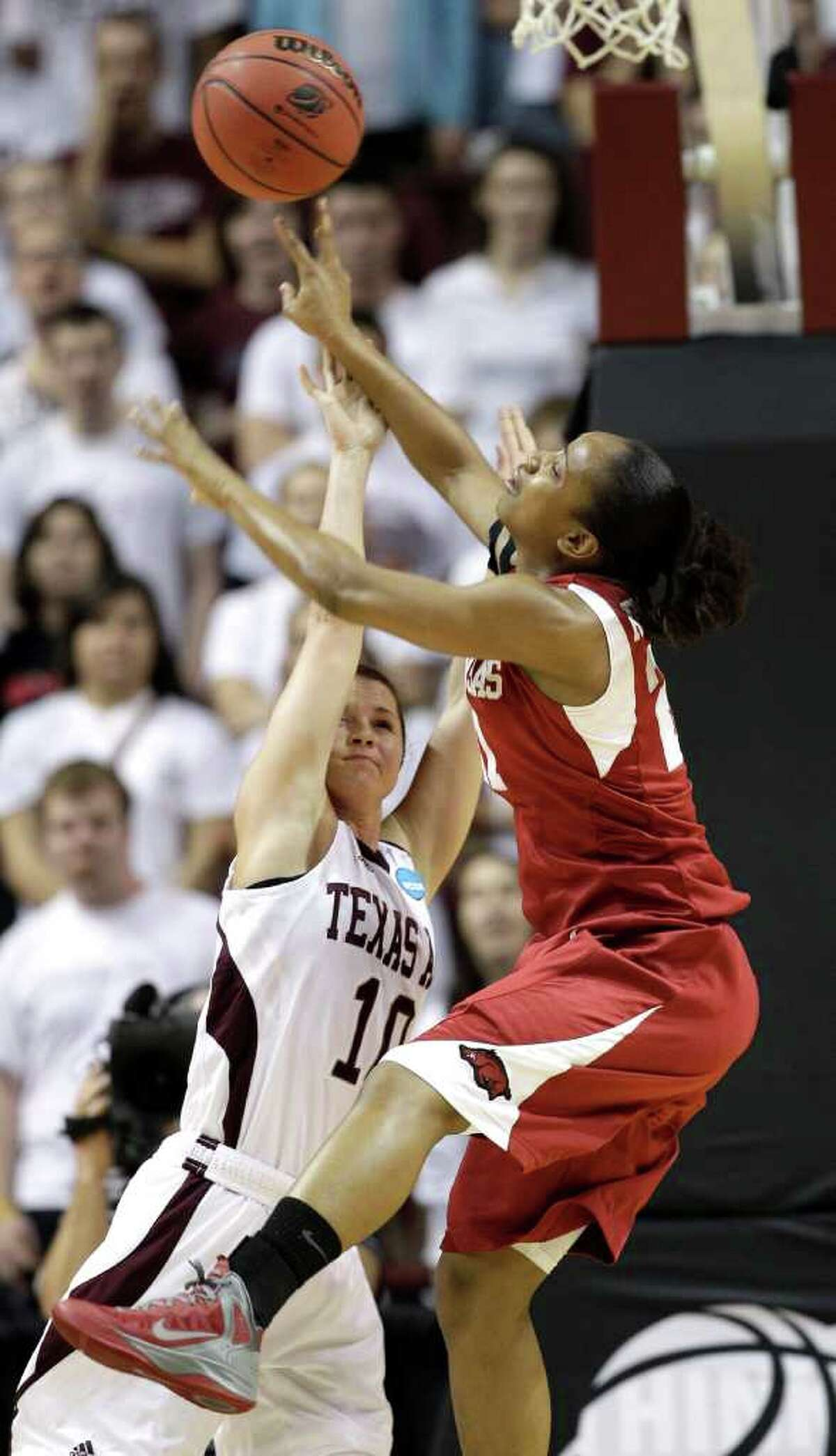 Texas A&M's Alexia Standish (10) goes up to block the shot of Arkansas' Dominique Robinson (21) during the first half of an NCAA tournament second-round women's college basketball game Monday, March 19, 2012, in College Station.