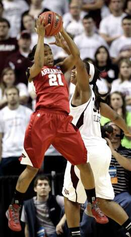 Arkansas' Dominique Robinson (21) pulls down a rebound in front of Texas A&M's Karla Gilbert (34) during the first half of an NCAA tournament second-round women's college basketball game Monday, March 19, 2012, in College Station. Photo: Associated Press