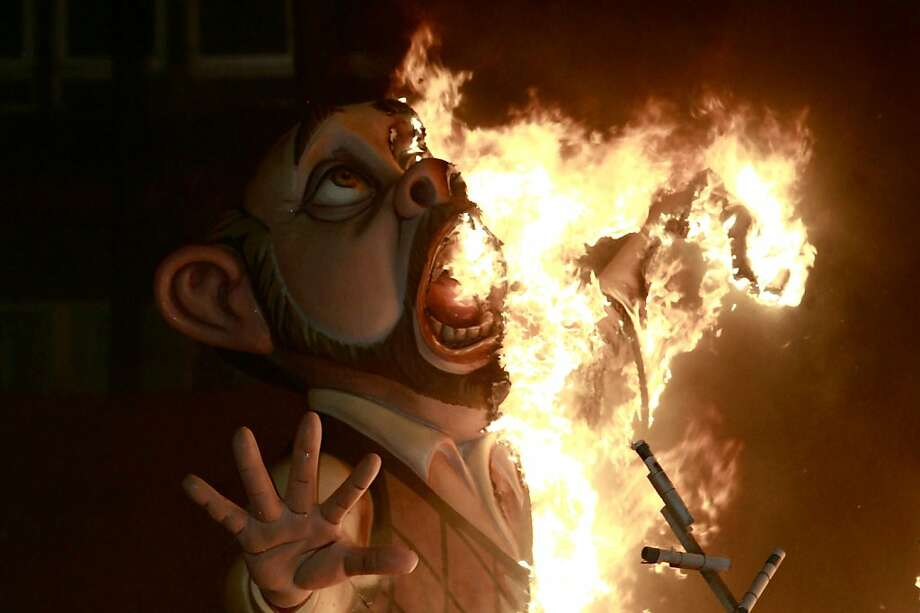 """Paper mache figures are burned during the Fallas festival in Valencia, Spain, in the early hours of Tuesday March 20, 2012. Every year the city of Valencia celebrates the ancient """"Las Fallas"""" fiesta, a noisy week that is full of fireworks and processions in honor of Saint Joseph which climaxes in the burning of large paper mache figures displayed around the streets of the city. (AP Photo/Alberto Saiz) Photo: Alberto Saiz, Associated Press"""