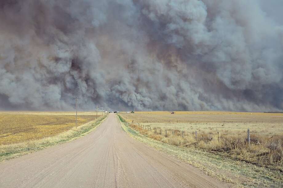 In a Sunday, March 18, 2012 photo provided by the Yuma, Colo., Pioneer, a wildfire sends up a huge wall of smoke, forcing authorities to temporarily close a section of U.S. Highway 34 east of Yuma County, Colo., when the fire filled the skies with so much smoke that firefighters couldn't see the flames. Evacuated residents of the small Colorado town of Eckley have been allowed to return home after firefighters contained most of the wildfire.  (AP Photo/The Yuma Pioneer, Tony Rayl) Photo: Tony Rayl, Associated Press