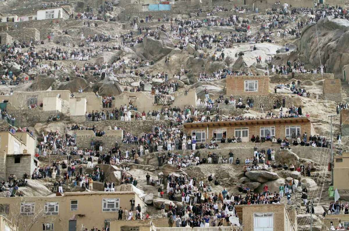 Afghans gather on a hillside to watch the raising of the holy mace, unseen, during a celebration of the Persian New Year Nowruz at the Kart-e-Sakhi shrine in Kabul, Afghanistan, Tuesday, March 20, 2012. Nowruz, the Farsi-language word for