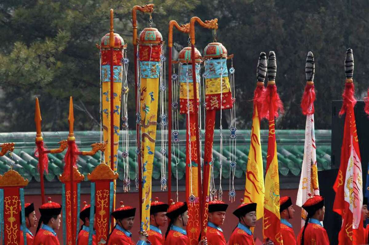 Performers prepare to take part in a re-enactment of a Qing Dynasty Emperor's prayer ceremony at a park in Beijing, China, Tuesday, March 20, 2012.