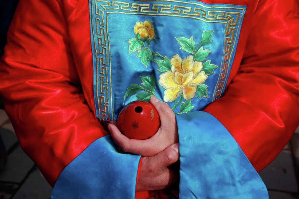 A musician wearing Qing dynasty-period costume holds a replica of a traditional wind instrument, waiting to take part in a re-enactment of a Qing Dynasty Emperor's prayer ceremony at a park in Beijing, China, Tuesday, March 20, 2012.
