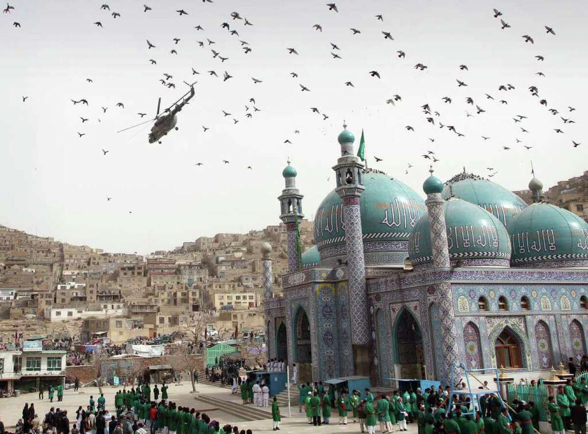 An Afghan military helicopter flies over the crowd gathered for a celebration of the Persian New Year Nowruz at the Kart-e-Sakhi shrine in Kabul, Afghanistan, Tuesday, March 20, 2012. Nowruz, the Farsi-language word for