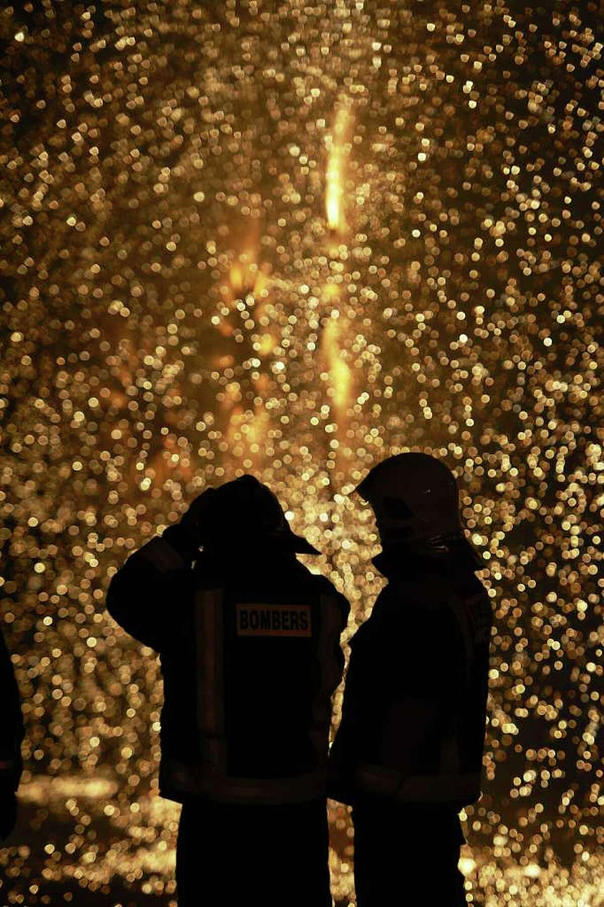 VALENCIA, SPAIN - MARCH 19: Firemen look on while a combustible 'Ninot' caricatures burn during the last day of the 'Fallas' festival on March 19, 2012 in Valencia, Spain. The festival, which runs March 15 - 19, celebrates the arrival of spring with fireworks, fiestas and bonfires.