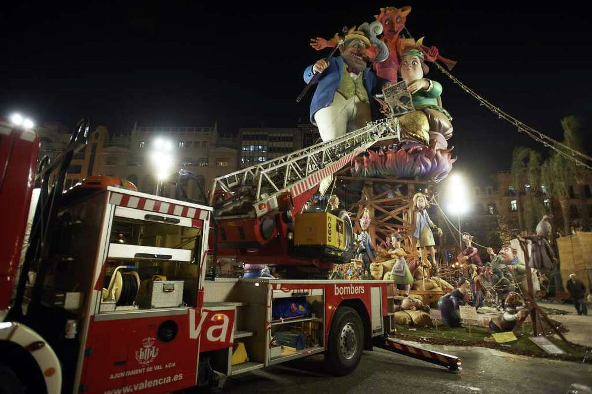 VALENCIA, SPAIN - MARCH 19: People prepare for the burning of the 'Ninot' caricatures during the last day of the 'Fallas' festival on March 19, 2012 in Valencia, Spain. The festival, which runs March 15 - 19, celebrates the arrival of spring with fireworks, fiestas and bonfires.