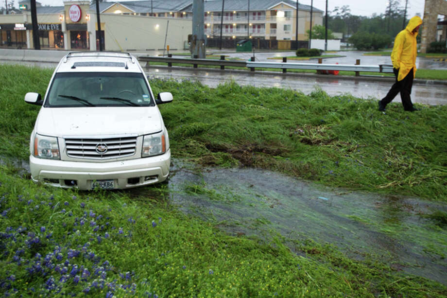 A vehicle sits in a ditch off the southbound lanes of Interstate 45 near Woodlands Parkway Tuesday, March 20, 2012, in Houston. (Brett Coomer / Houston Chronicle)