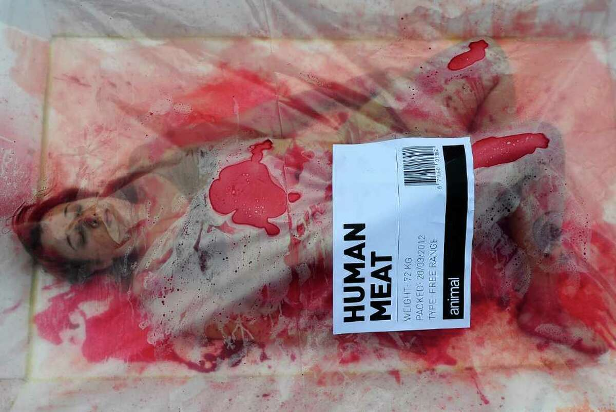 """An animal rights activist from the group 'Animal Equality' stages a protest during a """"Day Without Meat"""" event in Barcelona, Spain, Tuesday. (AP Photo/Manu Fernandez)"""