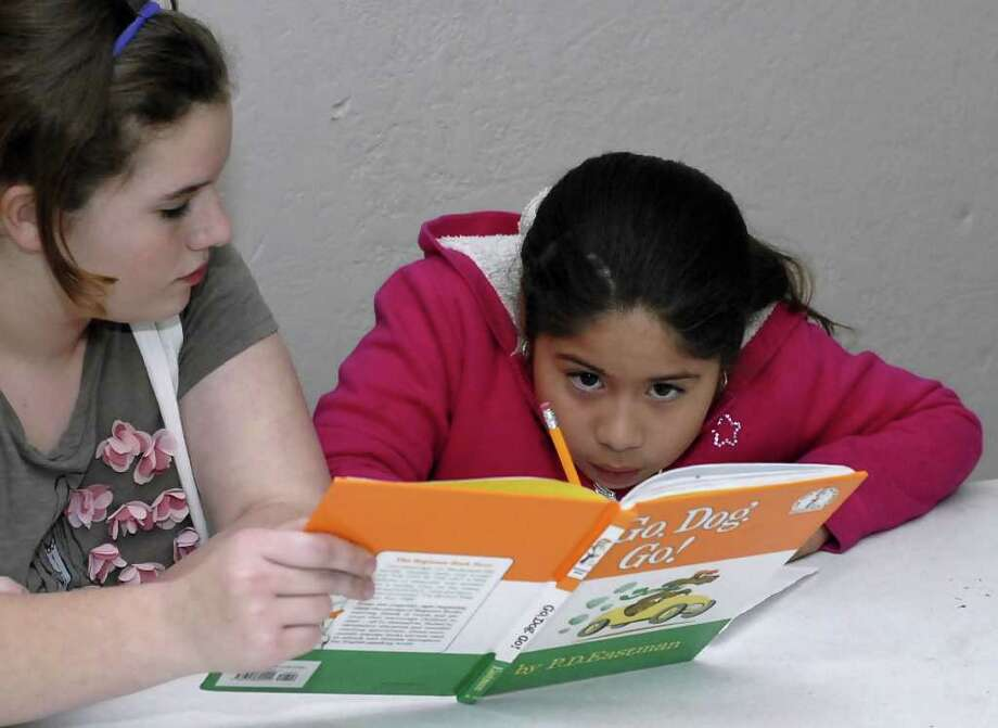 Thirteen-year-old Bleyl Middle School seventh-grader Kenzie David, left, volunteers as a reading tutor for 9-year-old Daisy Orduno at Cy-Hope's Hope Center after-school program in the Trails of Windfern Apartments. Photo: Tony Bullard / Tony Bullard & the Houston Chronicle