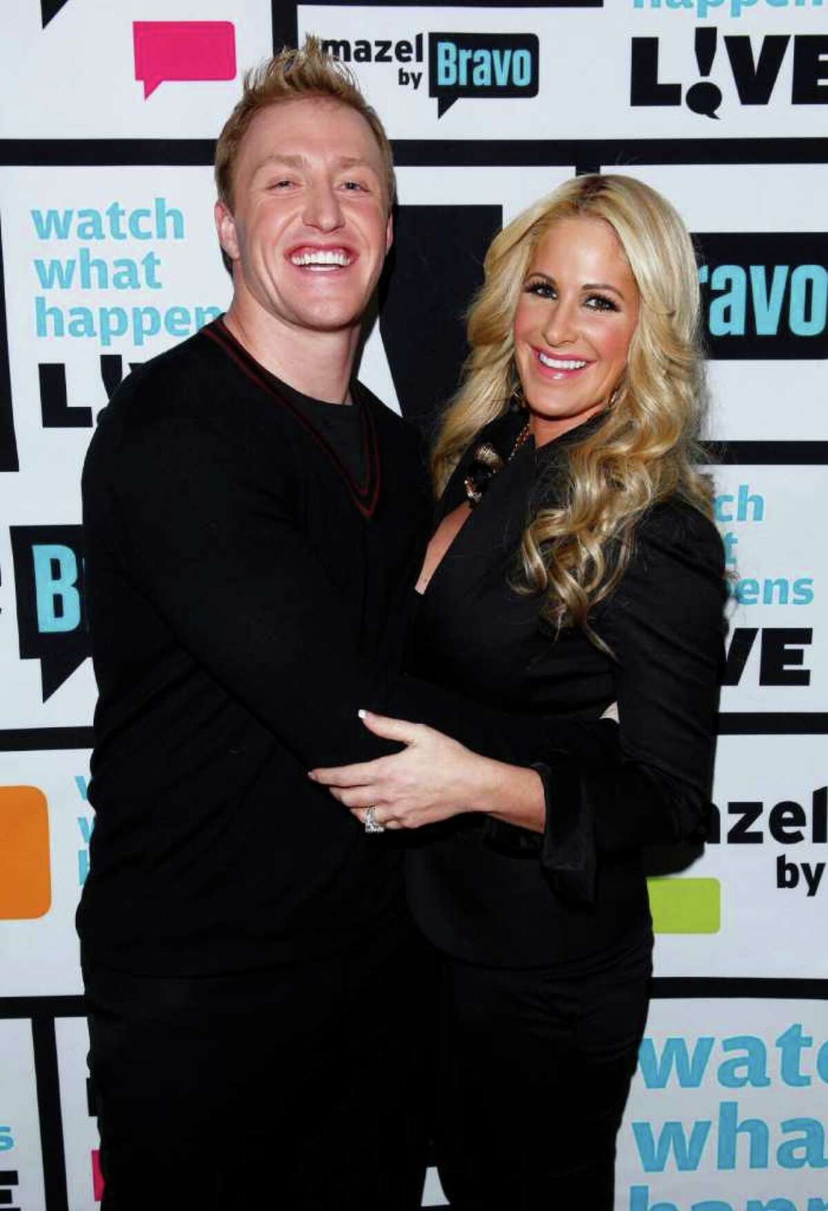FILE - In this Jan. 29, 2012 file image released by Bravo, Kroy Biermann, left, and Kim Zolciak pose backstage after Bravo's