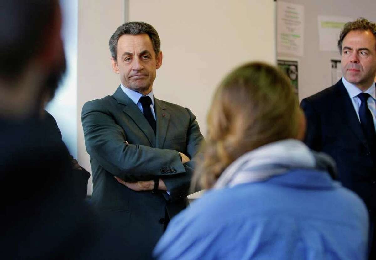 French President Nicolas Sarkozy, left, and Education Minister Luc Chatel, right, talk with pupils of the Francois Couperin College in Paris, in the classroom of their school, Tuesday, March 20, 2012, the day after a gunman on a motorbike opened fire at a Jewish school in the French city of Toulouse, southwestern France. Hundreds of police blanketed southern France on Tuesday, searching for a gunman, possibly a racist, anti-Semitic serial killer, who killed four people at a Jewish school and may have filmed his attack.(AP Photo/Jacques Brinon Pool)
