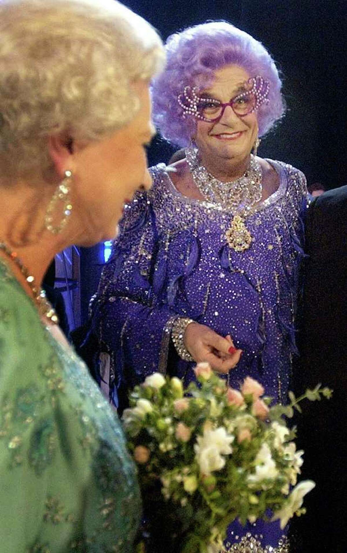 FILE-In this Nov. 24, 2003 file photo Britain's Queen Elizabeth II, left, meets Barry Humphries, aka Dame Edna Everage, at the Festival Theatre in Edinburgh for the start of the 75th Royal Variety performance in Edinburgh, Scotland. Dame Edna Everage, the Tony Award-winning drag act known for her purple hair and oversized rhinestone eyeglasses, will soon open her final stage show tour in Australia. (AP Photo/David Cheskin, Pool, File)