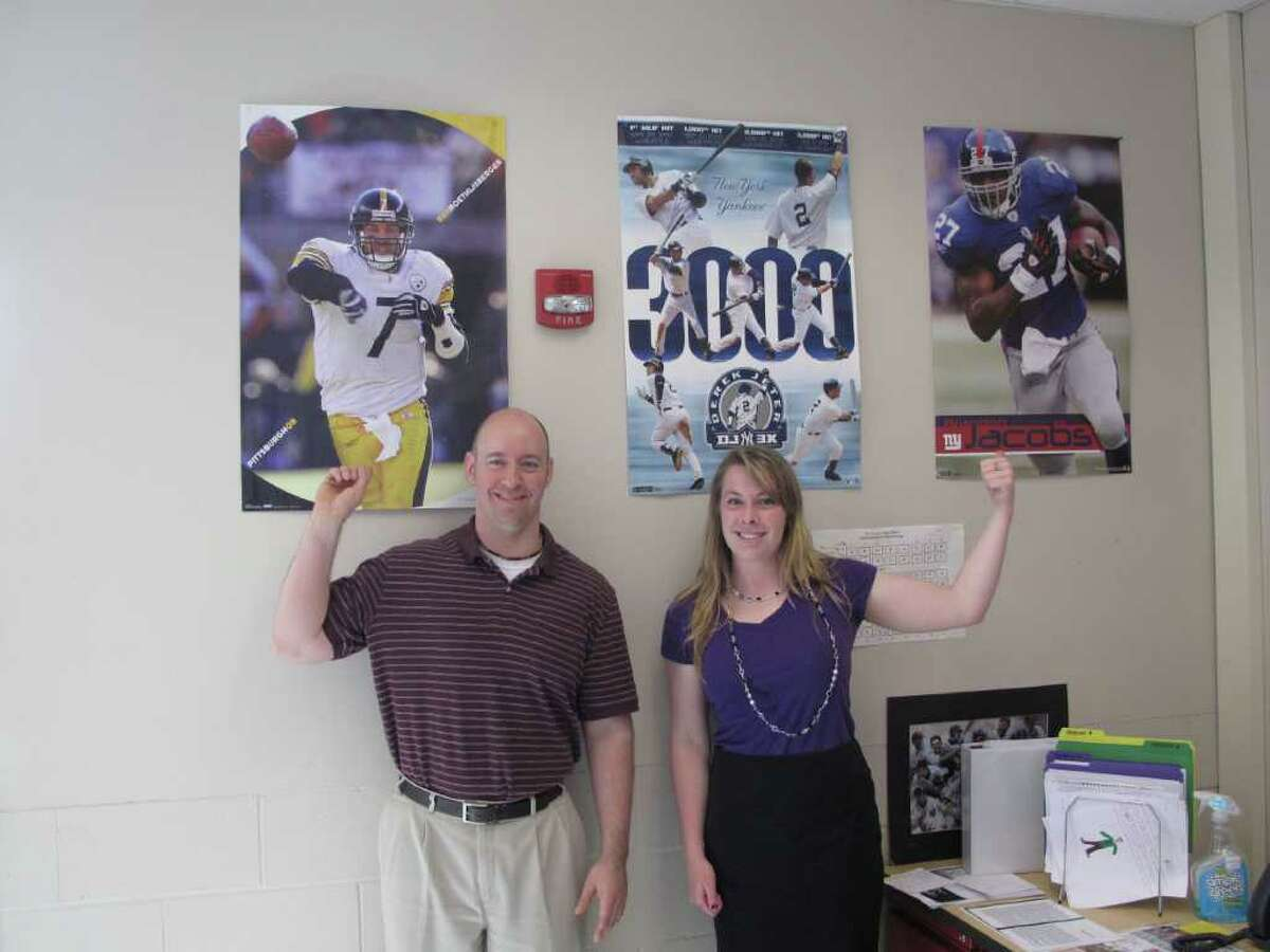 Aaron Gallo and Katherine Munson stand by their respective sports teams in the classroom where they teach an exciting new class about sports and literature.