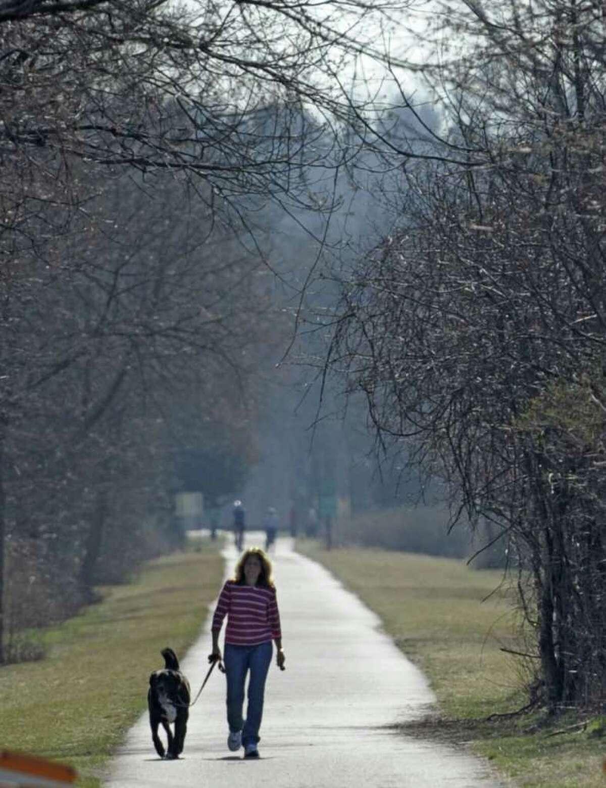 Veterinarian Debbie Snyder takes her dog Sundance for a walk on the bike path near Lions Park in Niskayuna, N.Y. March 20, 2012. (Skip Dickstein/Times Union)