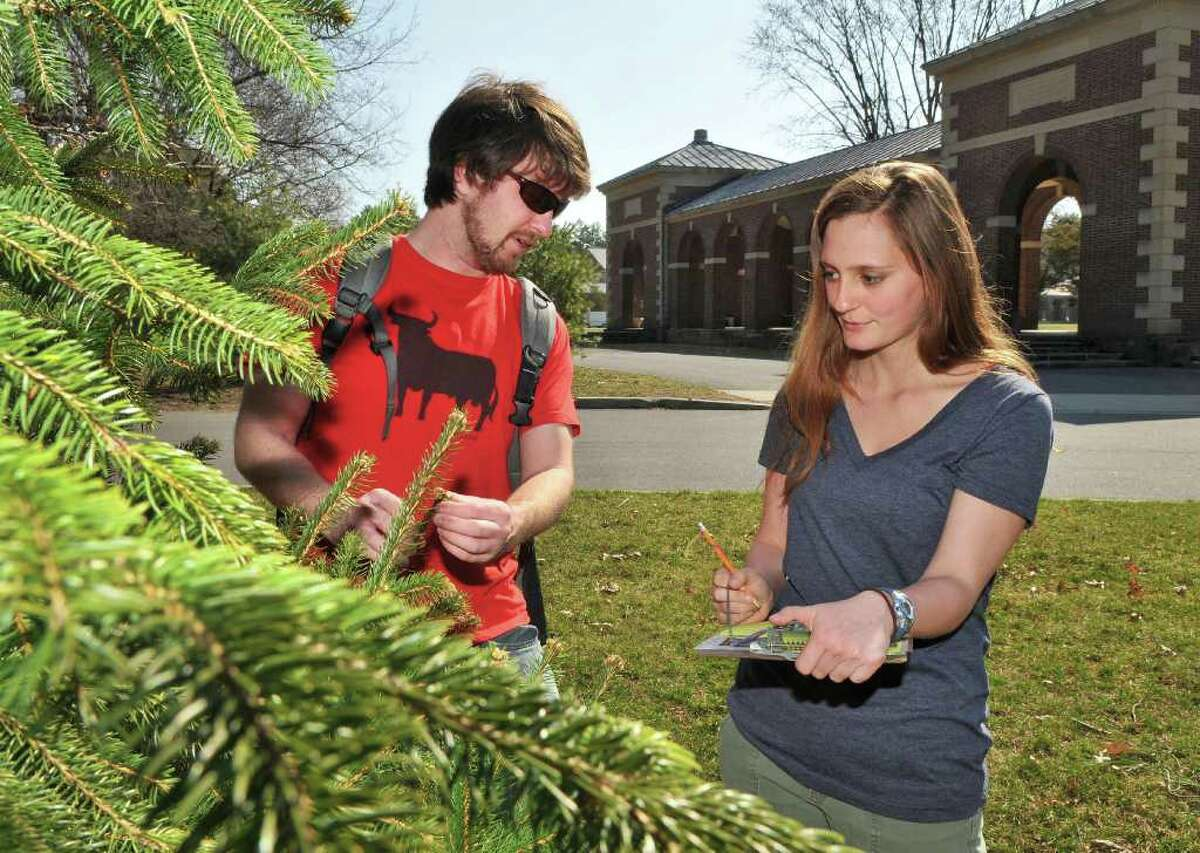 Wildlife ecology student Jeff Hyma, left, of Stevens Point, Wisc., and Carla Francis of Saratoga Springs, an Americorps intern at Saratoga Spa State Park, note signs of an early spring on a balsam fir in the park Tuesday March 20, 2012. (John Carl D'Annibale / Times Union)