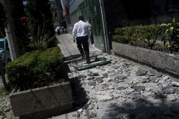 A man walks over the debris fell from a building in Mexico City damaged during a strong quake that hit Mexico on March 20, 2012. Photo: YURI CORTEZ, AFP/Getty Images / AFP