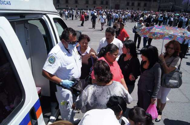 Paramedics give assistence to people gathered at the El Zocalo square in Mexico City after a strong quake hit Mexico on March 20, 2012. Photo: ANGEL GARCIA, AFP/Getty Images / AFP