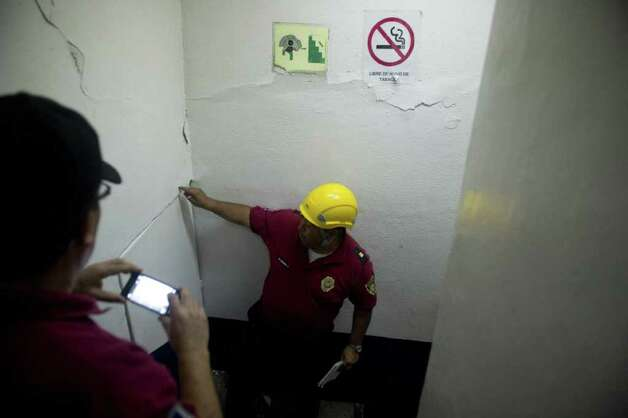 Experts make an inspection in a building of Mexico City damaged by a strong quake that hit Mexico on March 20, 2012. Photo: YURI CORTEZ, AFP/Getty Images / AFP