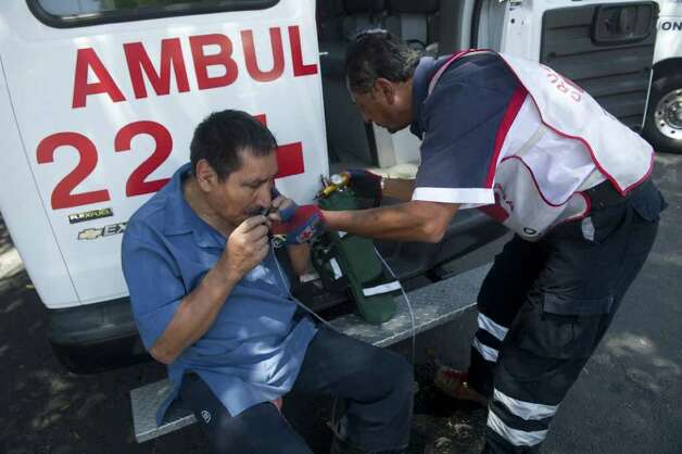A member of the Mexican Red Cross gives medical attention to a man in Mexico City following a strong quake that hit Mexico on March 20, 2012. Photo: YURI CORTEZ, AFP/Getty Images / AFP