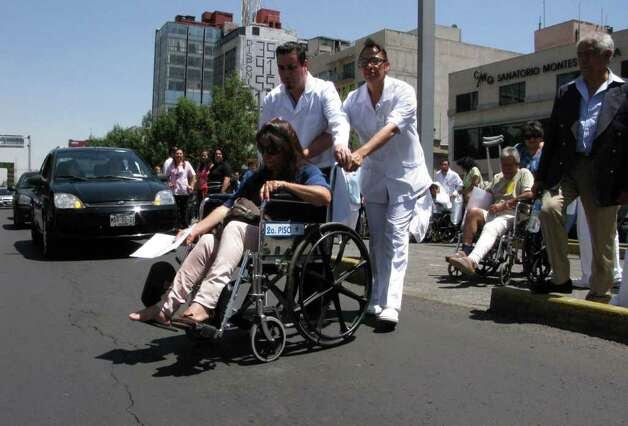 Patients are evacuated in wheelchairs from the Hospital de Chalpultepec after an earthquake was felt in Mexico City, Tuesday March 20, 2012.  (AP Photo/Marco Ugarte) Photo: Marco Ugarte, Associated Press / AP