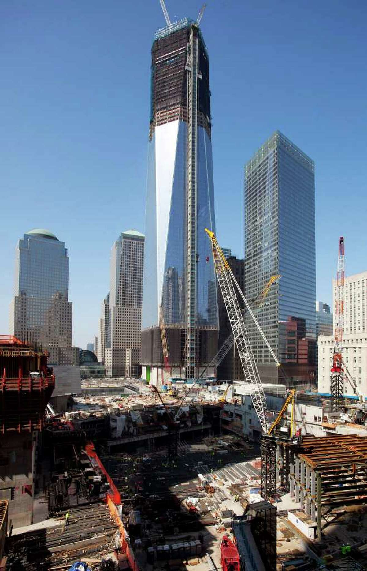 One World Trade Center, top, towers above construction of the transportation hub, bottom, Monday, March 19, 2012 in New York. The tower, now up to the 93rd floor, is expected to be completed in late 2013.
