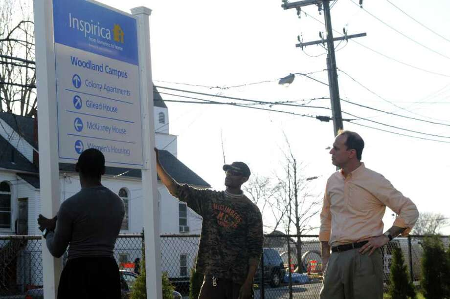 "Joshua Davis and Bobby Brand position the new sign as Chief Executive Officer Jason Shaplen examines its placement as what was St. Luke's LifeWorks transitions to it's new name ""Inspirica"" in Stamford, Conn., March 20, 2012. St. Luke's LifeWorks, which has served the area for 135 years, is rebranding itself with the new name ""Inspirica, from homeless to home."" Photo: Keelin Daly / Stamford Advocate"
