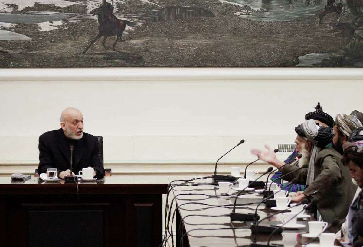 In this Friday, March 16, 2012 photo, Ghulam Rasool, right, a tribal elder from the Panjwai district of Kandahar province, gestures to Afghan President Hamid Karzai during a meeting at the presidential palace in Kabul. The motive for the March 11 shooting rampage that killed 16 Afghan civilians remains unclear, but villagers from the area are convinced that the killings were an act of revenge for a roadside bomb attack on American forces in the same area a few days before. (AP Photo/Ahmad Jamshid)
