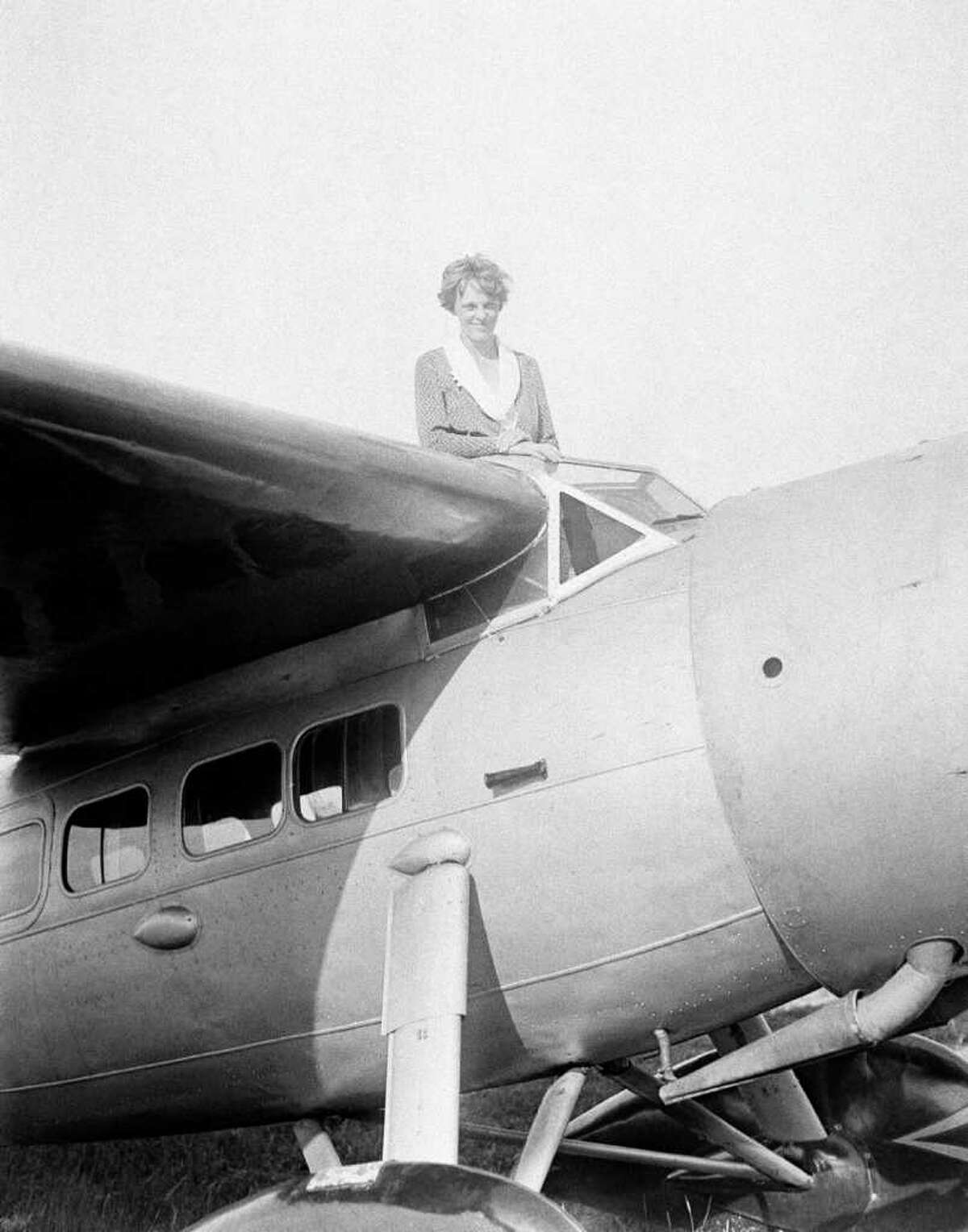 FILE - In this undated photo, Amelia Earhart, the first woman to cross the Atlantic Ocean by plane sits on top of a plane. Secretary of State Hillary Rodham Clinton is wading into one of the 20th century?'s most enduring mysteries: the fate of American aviator Amelia Earhart, disappeared over the South Pacific 75 years ago. Clinton is meeting March 20, 2012, with historians and scientists from The International Group for Historic Aircraft Recovery, which will launch a new search in June for the wreckage of Earhart?'s plane off the remote island of Nikumaroro. (AP Photo)