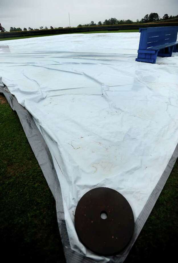 A tarp protects the West Brook softball field during heavy rains in Beaumont, Tuesday, March 20, 2012. Tammy McKinley/The Enterprise Photo: TAMMY MCKINLEY