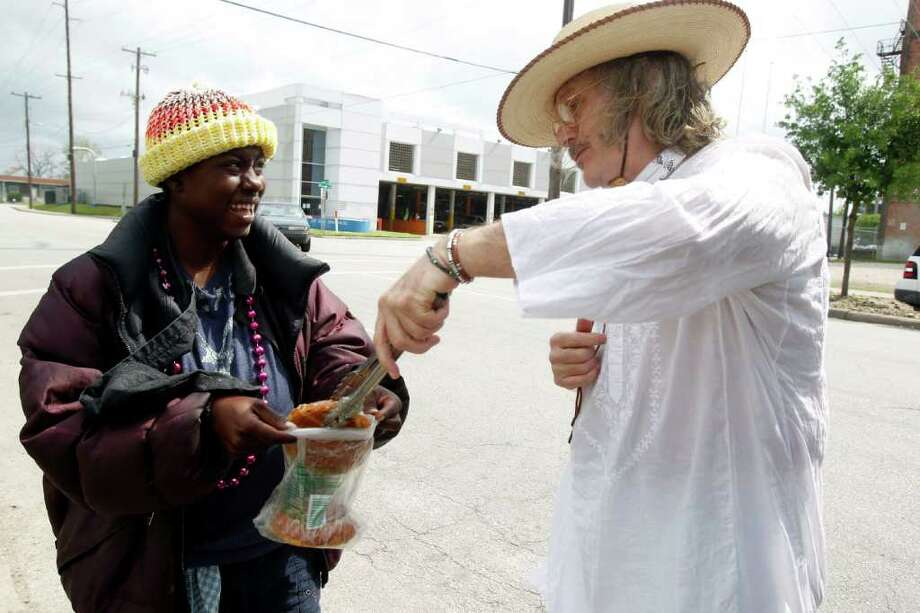 Jay Hamburger, right, who has been feeding the homeless for 21 years, provides pastries to Laneisha Bruton. Hamburger says city regulations could put him out of the charity business, since he is a one-man operation. Photo: James Nielsen / © 2012 Houston Chronicle