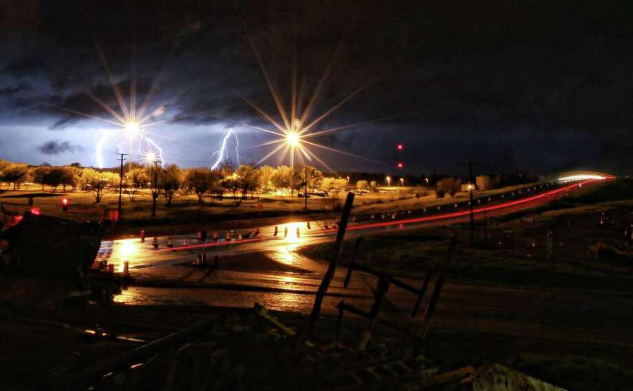 Lightning rips through the sky behind the Kimberly Clark plant in Paris, Texas Monday, March 19, 2012.  Photo: AP