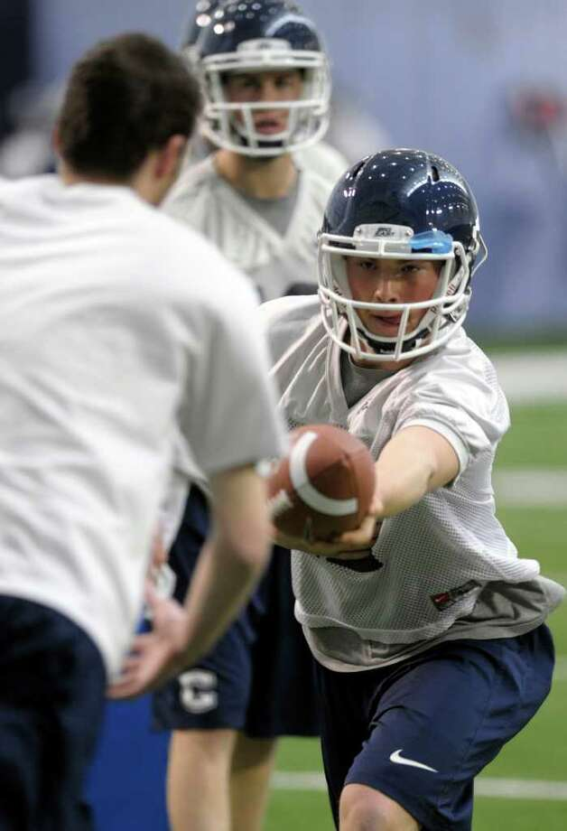 Connecticut quarterback Casey Cochran hands the ball off during the first day of the team's spring NCAA college football practice, Tuesday, March 20, 2012, in Storrs, Conn.  (AP Photo/Sean D. Elliot,The Day)   MANDATORY CREDIT: SEAN D. ELLIOT/THE DAY Photo: Sean D. Elliot, Sean D. Elliot/Associated Press Via The Day / 2012 The Day Publishing Company