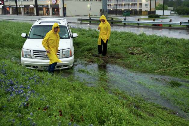 Tuesday's storm flooded streets and stranded vehicles, like this one stuck in a ditch off the southbound lanes of I-45 near Woodlands Parkway.  One consolation, though: Note the bluebonnets. Photo: Brett Coomer / © 2012 Houston Chronicle