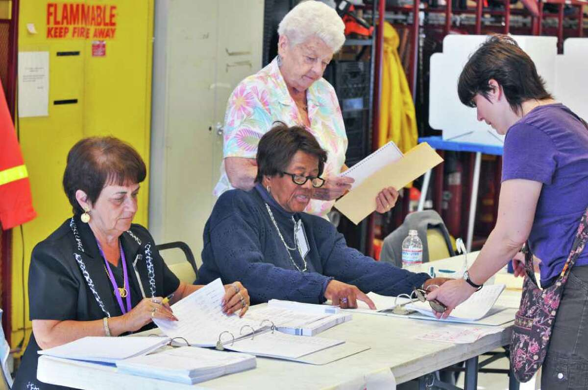 Juliet VanKampen, at right, signs in to vote in the village elections with election inspectors (from left) Elaine Habbinger, Geneva Conway and Bev Pach at the Menands Firehouse Tuesday March 20, 2012. (John Carl D'Annibale / Times Union)