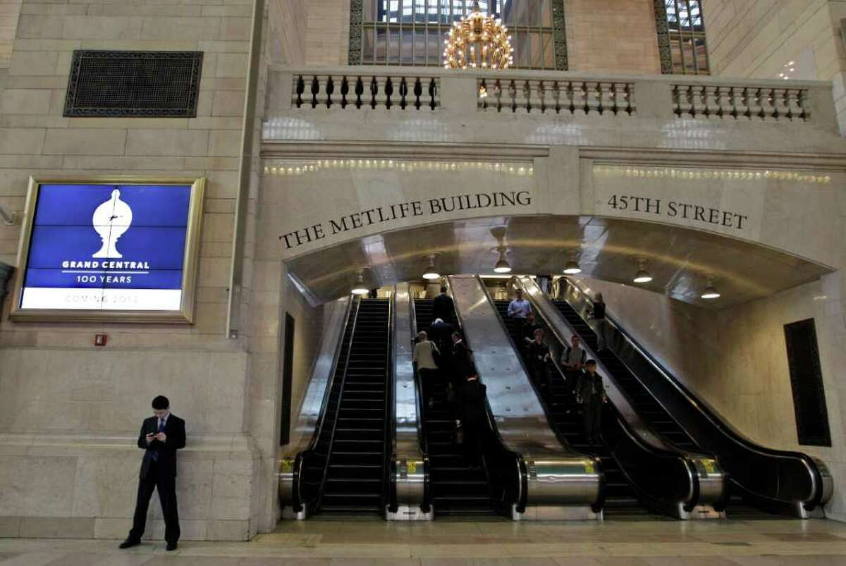 A commuter stands under the new Grand Central Terminal logo on display in the main concourse, Tuesday, March 20, 2012 in New York. Metropolitan Transportation Authority officials unveiled Grand Central Terminal's new logo Tuesday, and previewed plans to mark the terminal's 100th anniversary in 2013. (AP Photo/Mary Altaffer)