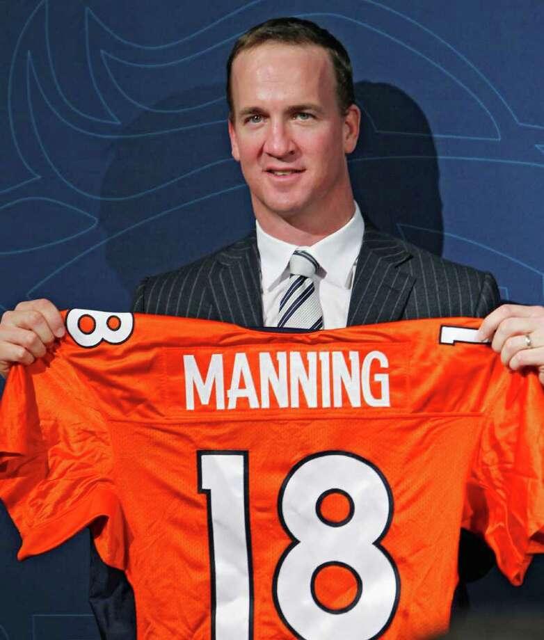 New Denver Broncos quarterback Peyton Manning holds a Broncos jersey with his name and number at the conclusion of an NFL football news conference at the Broncos headquarters in Englewood, Colo.,  on Tuesday, March 20, 2012.  (AP Photo/Ed Andrieski) Photo: Ed Andrieski