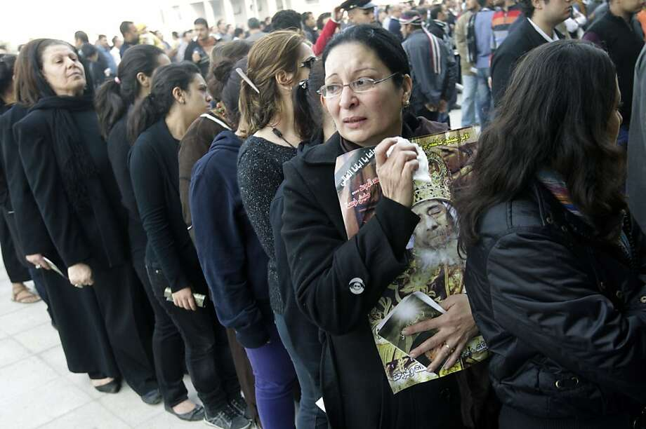 An Egyptian Christian woman carries a poster of the late Pope Shenouda III, the patriarch of the Coptic Orthodox Church who led Egypt's Christian minority for 40 years during a time of increasing tensions with Muslims, as others line up to enter his funeral at Mar Morqos, or St. Mark Coptic Orthodox Church in Cairo, Egypt, Tuesday, March 20, 2012. (AP Photo/Amr Nabil) Photo: Amr Nabil, Associated Press