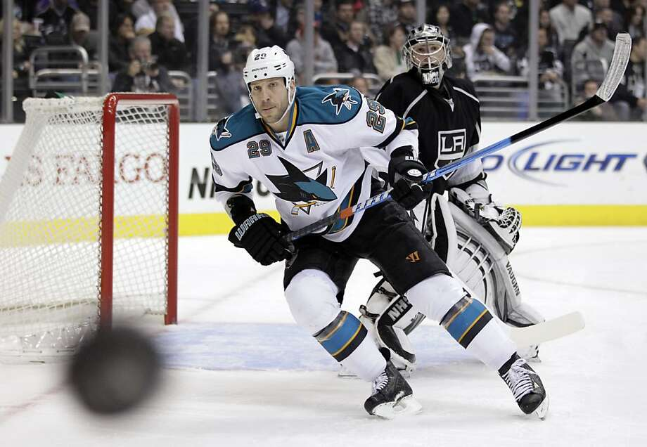 San Jose Sharks left wing Ryane Clowe and Los Angeles Kings goalie Jonathan Quick, background, look at the puck during the first period of an NHL hockey game in Los Angeles, Tuesday, March 20, 2012. Photo: Jae C. Hong, Associated Press