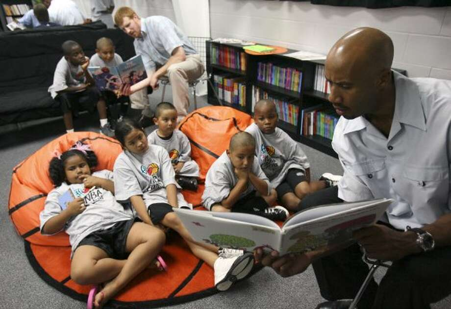 FOR NBR - Spurs' Matt Bonner (rear) and teammate Bruce Bowen read to children Friday June 8, 2007 during the dedication of the newly completed Reading & Learning Center at the Copernicus Community Center. PHOTO BY EDWARD A. ORNELAS/STAFF (SAN ANTONIO EXPRESS-NEWS)