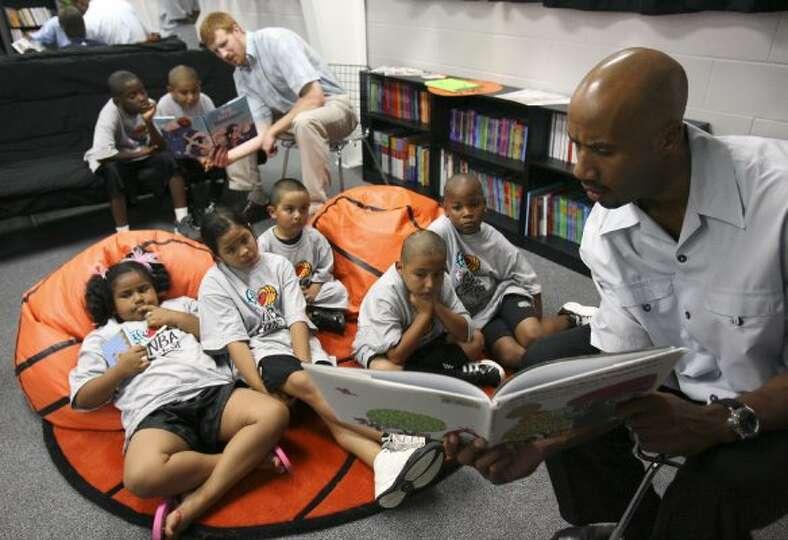 FOR NBR - Spurs' Matt Bonner (rear) and teammate Bruce Bowen read to children Friday June 8, 2007 du