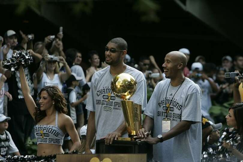 METRO - Tim Duncan, left, and Bruce Bowen, right, pass cheering fans on the parade route during the