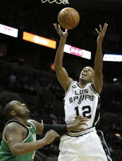 Spurs' Bruce Bowen (12) reacts while grabbing a rebound against the Boston Celtics' Glen Davis (11)