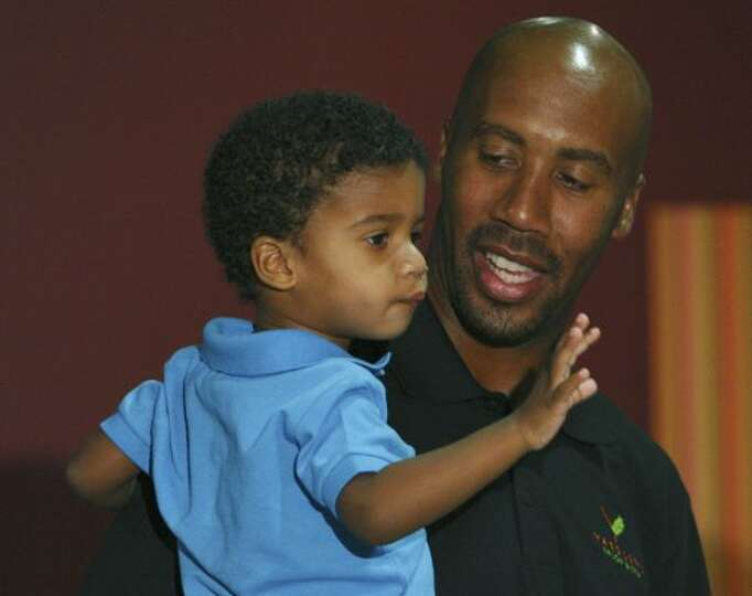 FOR SPORTS - Former Spurs' player Bruce Bowen holds his son Ojani Bowen, 3, prior to a press confere