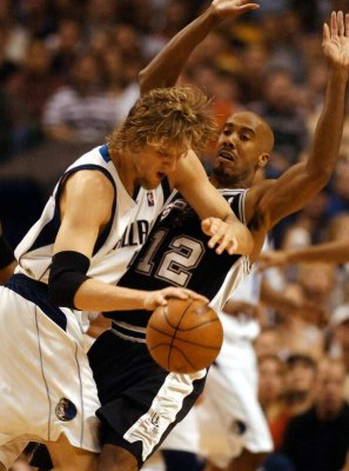 Mavs Dirk Nowitzki drives against the defense of Spurs Bruce Bowen (12) during first quarter action in game three of the Western Conference Finals at the American Airlines Arena in Dallas May 23, 2003. JERRY LARA/STAFF (SAN ANTONIO EXPRESS-NEWS)