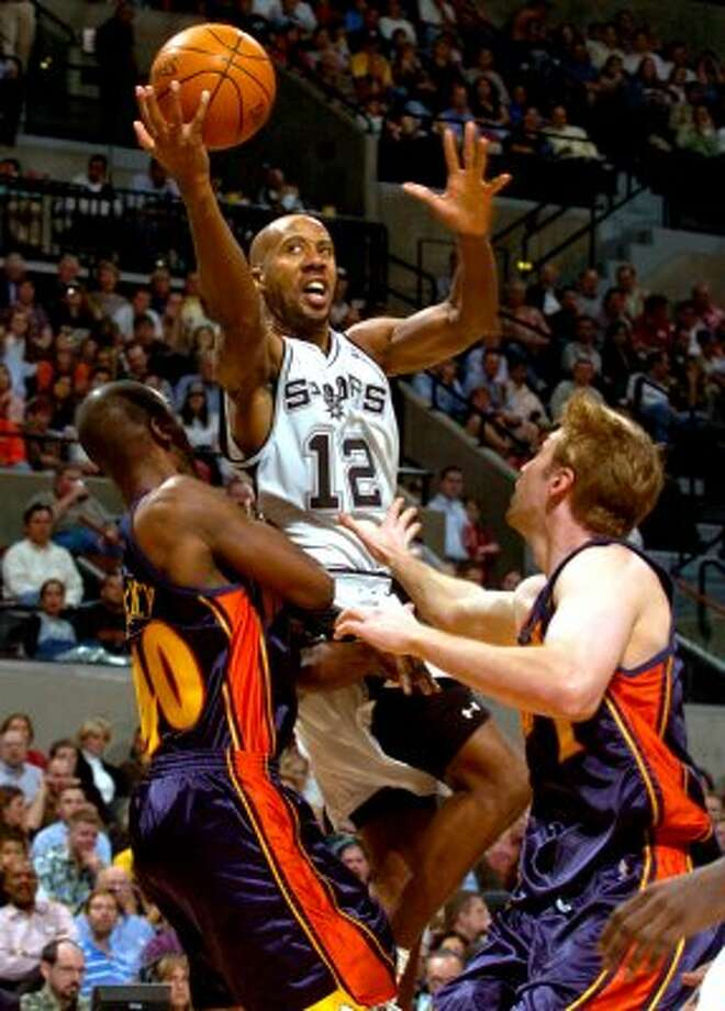 SPORTS   ---   The Spurs' Bruce Bowen drives Wednesday night Nov. 10, 2004 at the SBC Center in San Antonio past the Warriors' Calbert Cheaney, left, and Troy Murphy on the way to the hoop.   (WILLIAM LUTHER/STAFF) (SAN ANTONIO EXPRESS-NEWS)