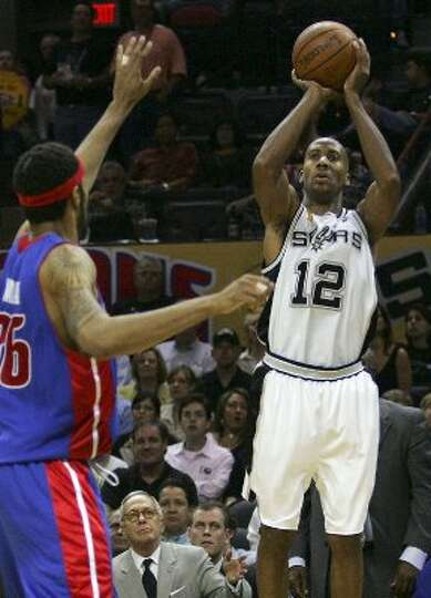 Spurs Bruce Bowen shoots a three point shoot past the defense of Pistons Rasheed Wallace during thir